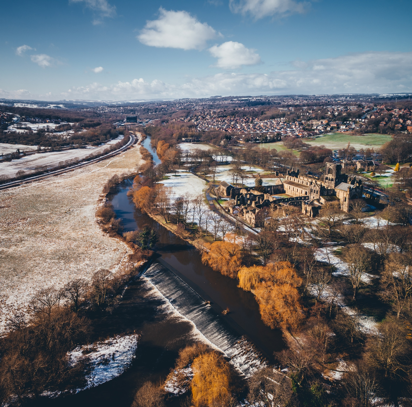 Kirsktall Abbey photographed from a drone in Winter, the river runs alongside it with snow and ice built up along its edges