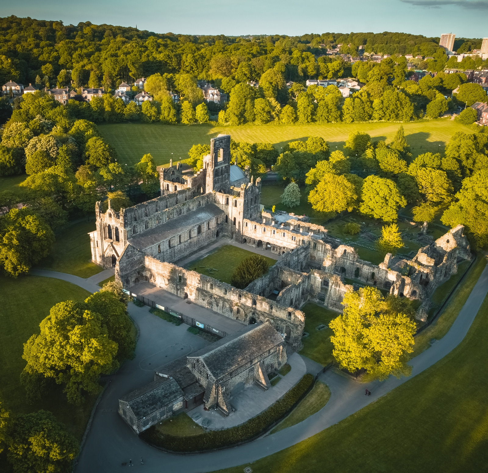 A closeup aerial shot of Kirkstall Abbey filmed in the last light of summer. It is surrounded by trees and green fields