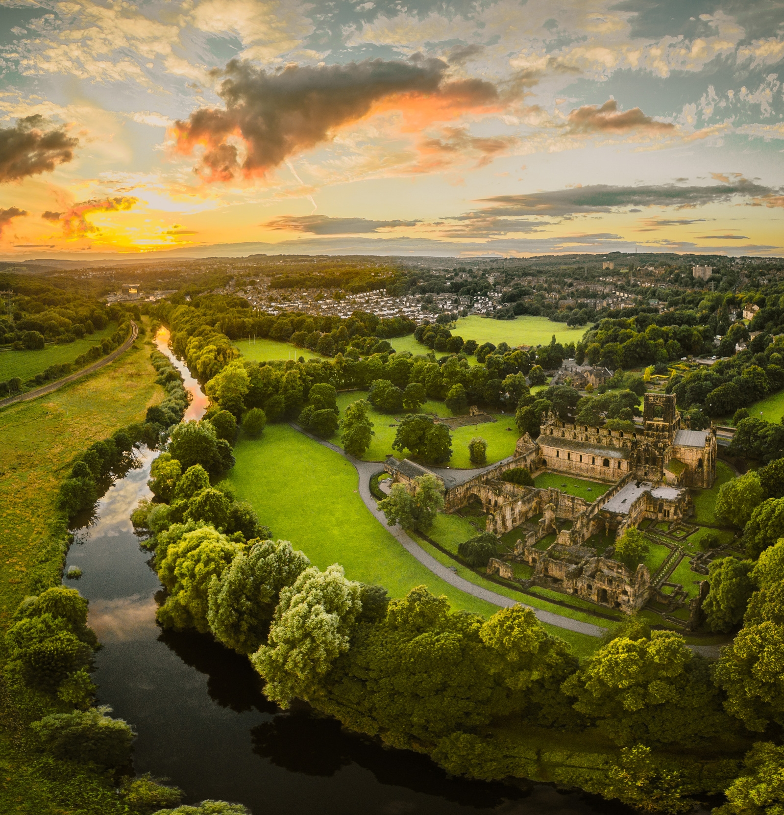 Kirkstall Abbey in summer sunshine surrounded by a ring of green lush trees