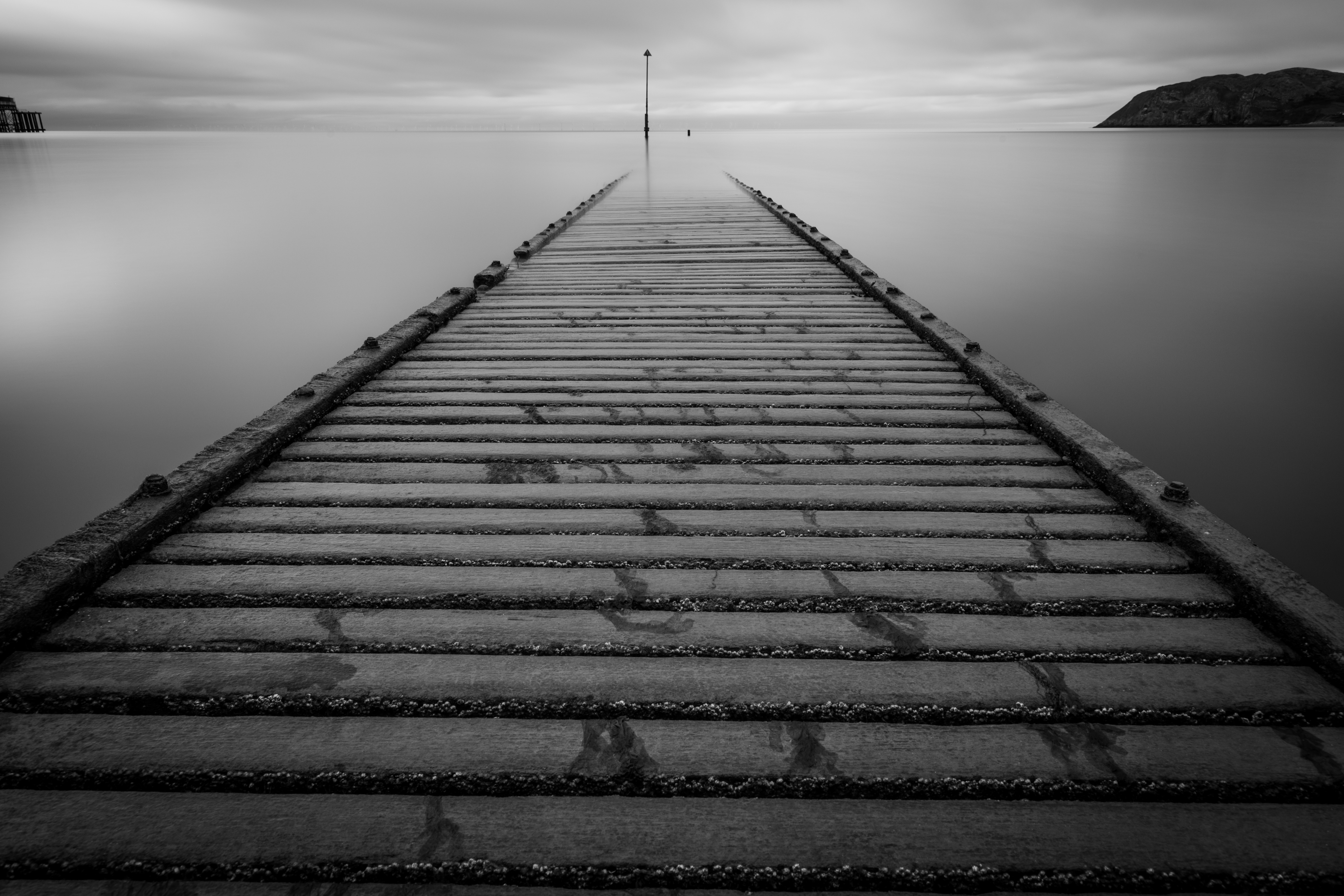 A long exposure of boardwalk in Llandudno leading out to perfectly still water in the distance.