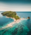 A hilly island in the middle of the sea photographed from a drone. The island hs small beach covers around it where people are sunbathing